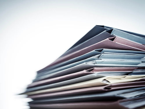 Stack of multicolored folders sitting on a desk