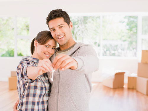 Man and a woman holding the keys to their new home